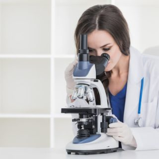 白衣をきている女性が顕微鏡で何かを調べている