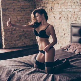 黒い下着を着ている女性がベッドの上でセルフィーしている